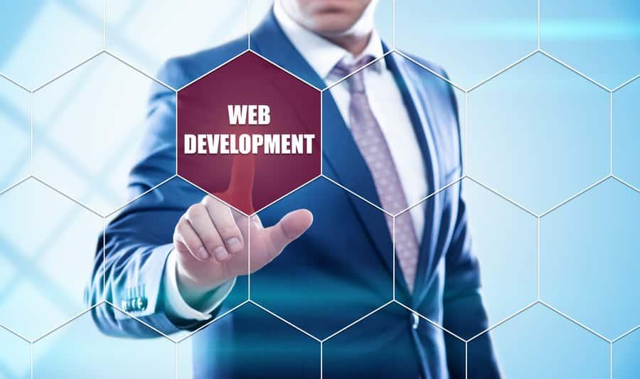 Geschäftsmann, drückt Web Development Knopf auf virtuellen Bildschirm