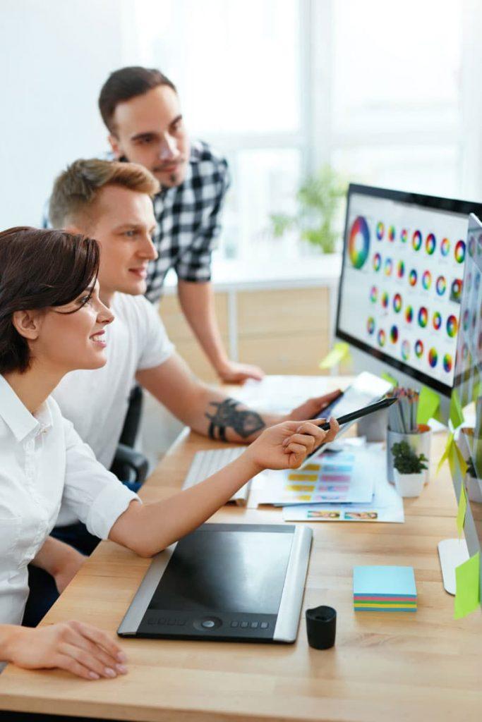 2 Herren und eine Frau sehen auf Desktop mit Farbkombinationen
